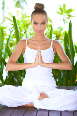 Beautiful glamorous woman practising yoga sitting in the lotus position with her hands together as though in prayer Stock Photo - 13857751
