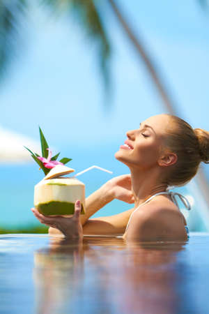 fruit of the spirit: Beautiful blonde woman relaxing in pool holding a tropical fruit cocktail with her head back and eyes closed in bliss Stock Photo