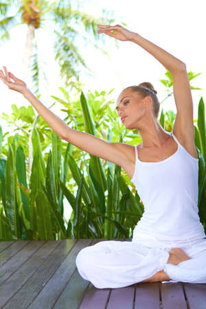 Beautiful graceful woman sitting cross legged on a deck bending her arms sideways while doing a yoga workout