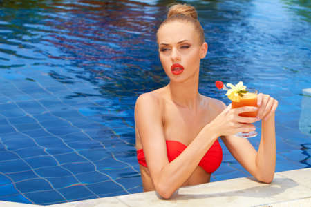 Beautiful blonde woman in a red bikini standing in a pool with a tropical cocktail photo