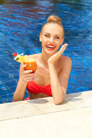 poolside: Laughing blonde woman in a pool with a large glass of tropical alcoholic cocktail in her hand