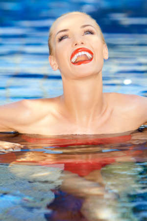 Laughing woman with her head thrown back relaxing in a sparkling blue pool photo