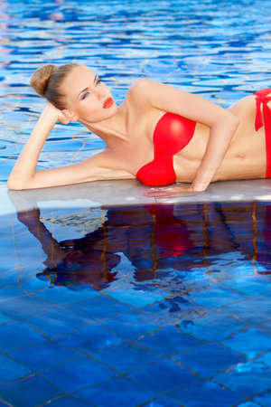 Pretty blonde in red bikini reclining on a concrete divider beside the swimming pool photo