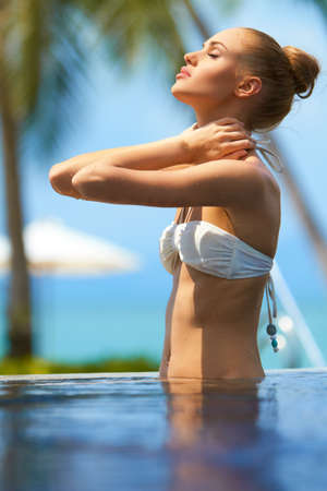 poolside: Pretty girl massaging her neck after a workout in a swimming pool