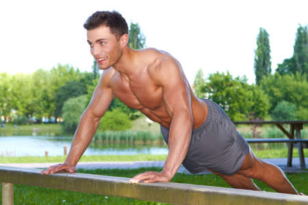 Fitness man in park making push ups in park photo