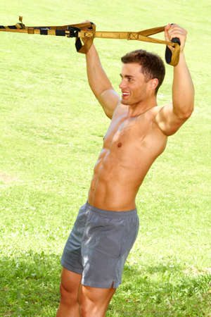Portrait of good looking fitness man in park photo