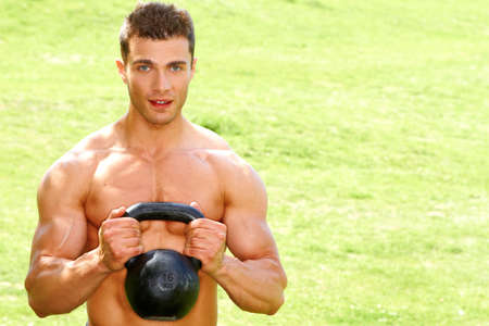 Muscular man holding kettlebell on grass background photo