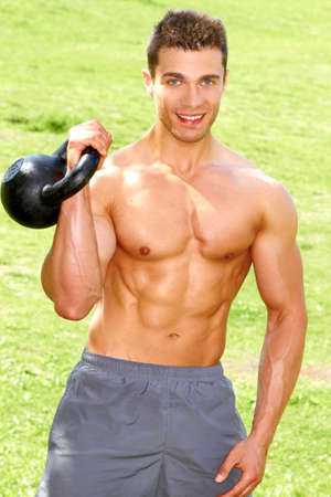 Fitness Man Working with kettlebell at outdoor photo