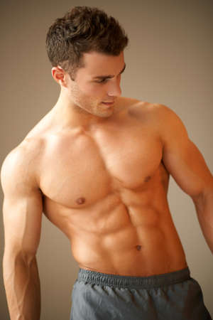Portrait of a handsome young man with great physique posing on natural background photo