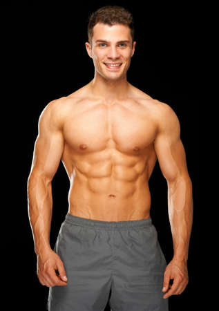 Portrait of muscular sporty man standing on black background photo