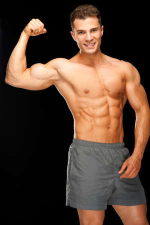 Portrait of confident muscular man flexing his biceps on black background Stock Photo - 14037098