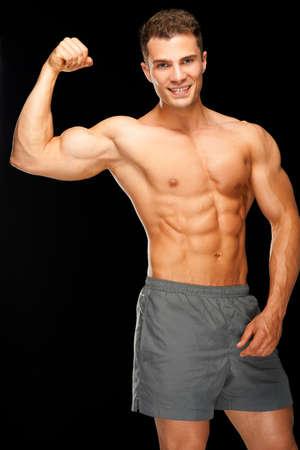 hombres sin camisa: Retrato de hombre musculoso confianza flexionando sus bíceps sobre fondo negro