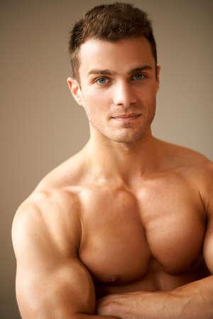 bel homme: Gros plan de l'homme sportif, avec des bras muscl�s crois�s sur fond brun