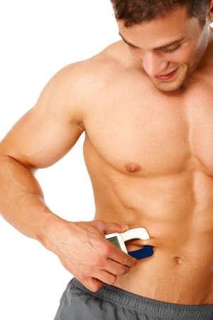 salud y deporte: Hombre guapo mide el nivel de grasa en su cuerpo en el fondo blanco