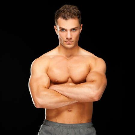 hombre sin camisa: Hombre guapo con los brazos cruzados mirando a su izquierda, sobre fondo negro