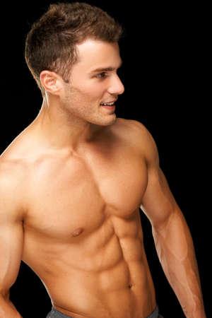 hombre sin camisa: Retrato de un atleta musculoso hombre aislado en un fondo negro