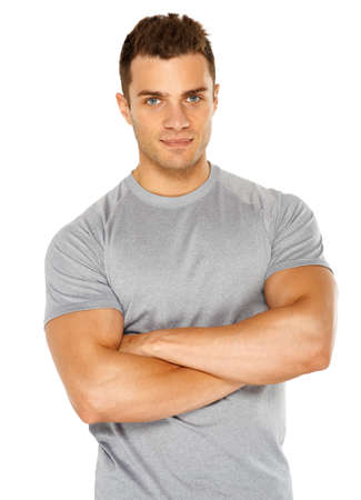Happy fit male with arms crossed posing over white background