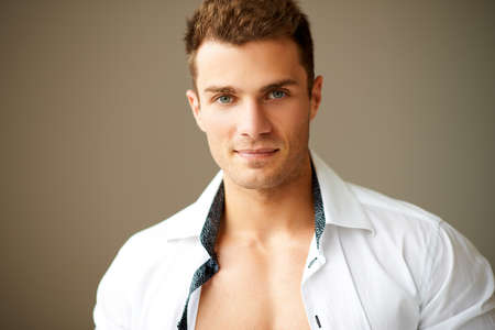 Close up of sporty man posing in white shirt over brown background