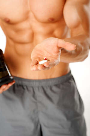 supplements: Close up of muscular man torso with hand full of pills on white