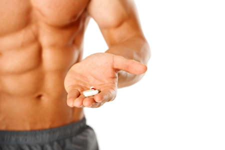 Close up of muscular man torso with hand full of pills on white photo