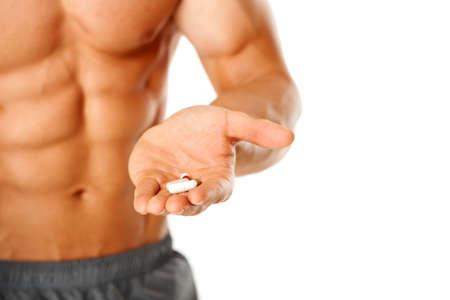 vitamina a: Primer plano del torso de hombre musculoso con la mano llena de pastillas en blanco