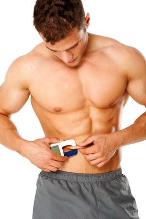 Muscular man measures level of fat on his body on white background photo