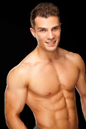 hombres sin camisa: Hermoso hombre musculoso joven aislado en fondo negro Foto de archivo