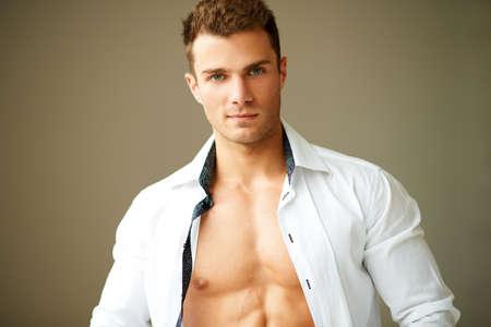 musculo: Retrato de hombre musculoso posando en camisa blanca sobre fondo marr�n Foto de archivo