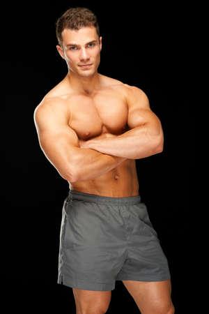 musculoso: Retrato de hombre joven y guapo de pie sobre fondo negro