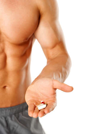 supplements: Part of muscular man torso with hand full of pills on white