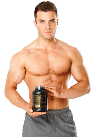 supplements: Muscular man holding black container of training supplements Stock Photo