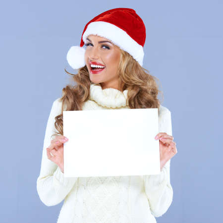 advertisment: Happy woman in Santa hat holding blank board with copyspace