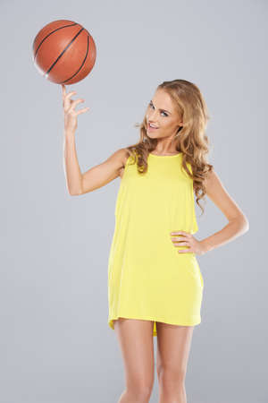 Cute blond woman posing and spin basket ball on her finger photo