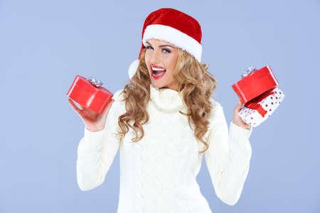 セクシーな女性サンタの帽子を選択するどのギフトを決定しよう 写真素材