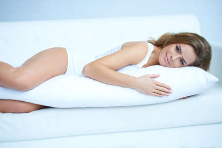 lying on stomach: Young pregnant woman laying on white sofa Stock Photo