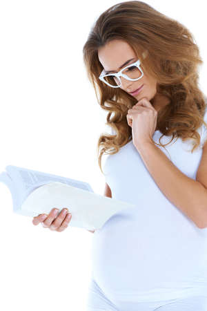 Cute young preganant woman reading a book on white