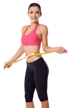 Attractive happy slim woman with a shapely body measuring her waist with a tape measure to confirm her weightloss Stock Photo