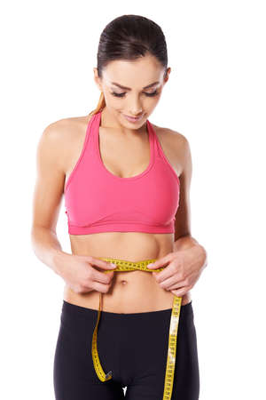 woman measuring waist: Young attractive slim female athlete measuring her waist with a tape meaure to check on her weightloss isolated on white