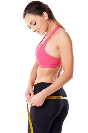 Sexy young woman athlete in sportswear standing measuring her hips with a tape measure isolated on white