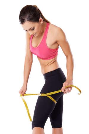 muslos: Fuerte hermoso joven atleta femenina que mide su muslo con una cinta métrica, tres retrato trimestre en blanco