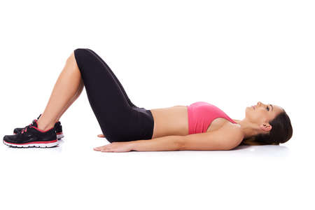 Fit young woman in gym clothes lying on her back on the floor with her knees raised exercising for health and vitality, studio portrait on white Stockfoto