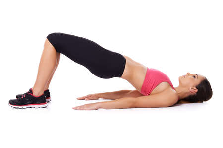 Fit woman doing exercises lying on her back on the floor raising her knees and body in the air, studio over white