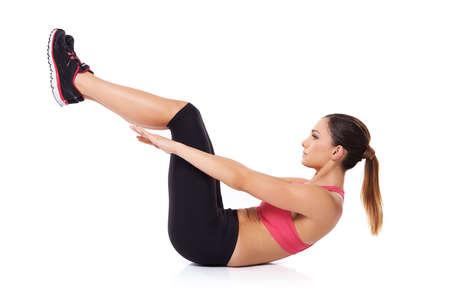 abdominal fitness: Mujer execising sus músculos abdominales acostado sobre su espalda en el suelo haciendo abdominales mientras mantiene sus piernas levantadas en el aire sobre blanco