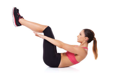sit ups: Woman execising her abdominal muscles lying on her back on the floor doing sit ups while holding her legs raised in the air over white