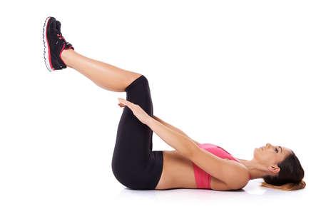 abdominal fitness: Mujer joven en forma saludable haciendo ejercicios acostado de espaldas sobre el suelo levantando sus piernas en el aire retrato de estudio, sobre el blanco