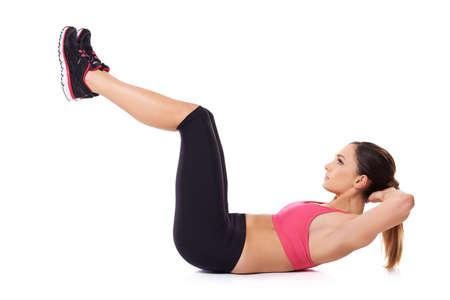 abdominal fitness: Montar mujer el ejercicio de sus músculos abdominales acostado de espaldas sobre el suelo levantando sus piernas y la cabeza en el aire retrato de estudio, sobre el blanco Foto de archivo