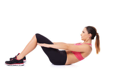 Fit jeune femme travaillant dans une salle de gym faire des redressements assis pour renforcer ses muscles abdominaux sur blanc Banque d'images