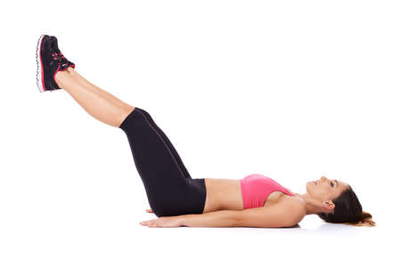 Woman doing leg lifts to strengthen her abdominal muscles while lying on the floor working out, studio portrait over white photo