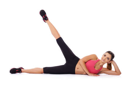 strengthen: Beautiful woman doing a workout lying on her side on the floor with her leg raised in the air to exercise and strengthen her muscles