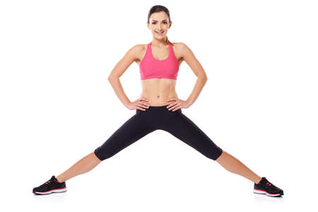 legs spread: Bella giovane atleta in posa con le gambe divaricate e le mani sui fianchi come sorride alla macchina fotografica